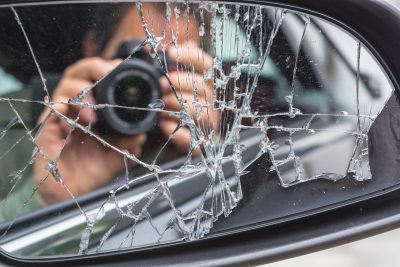 Spieglebild eines Fotograf im zerbrochenen Auto Spiegel.